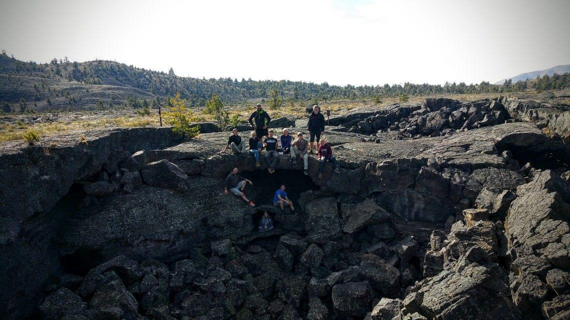 A group of students pose for a picture on top of a crumbled lava tube
