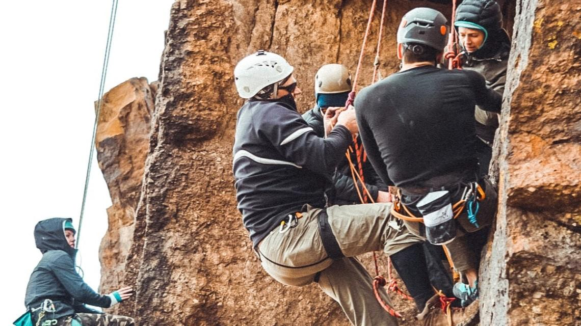 A group of students get ready to start scaling a cliff route