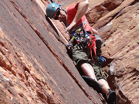 rock climber reaches for equipment on his hip